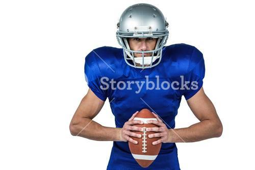 Confident American football player holding ball