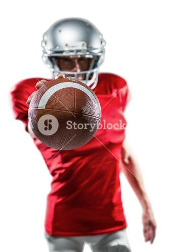 Confident American football player in red jersey holding ball
