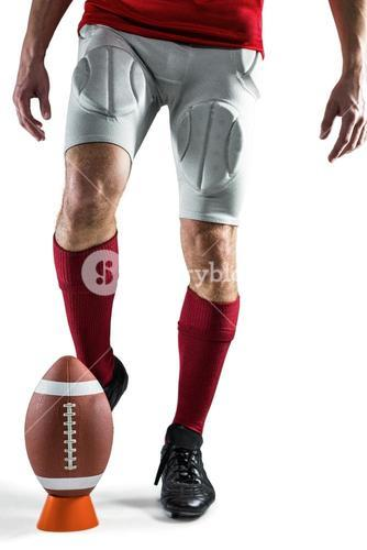 Low section of sports player kicking ball