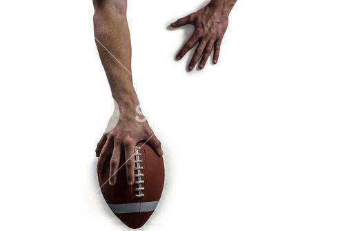 Cropped image of American football player holding ball
