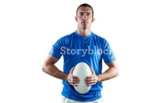Handsome rugby player in blue jersey holding ball