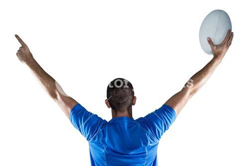 Rear view of rugby player holding ball with arms raised