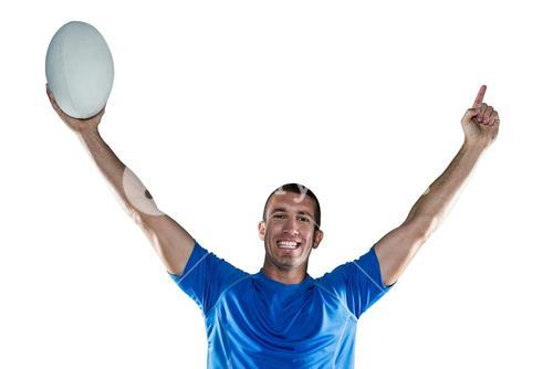 Portrait of rugby player in blue jersey holding ball with arms raised