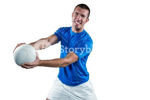 Portrait of smiling rugby player in blue jersey holding ball