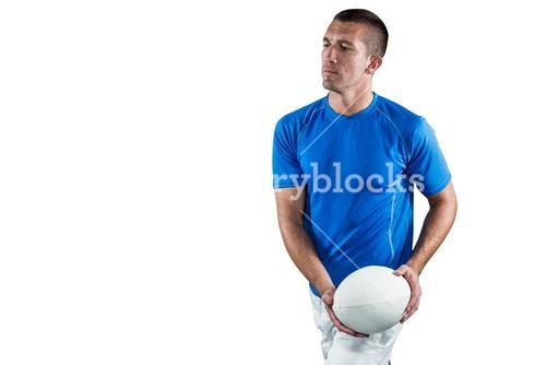 Serious rugby player in blue jersey holding ball