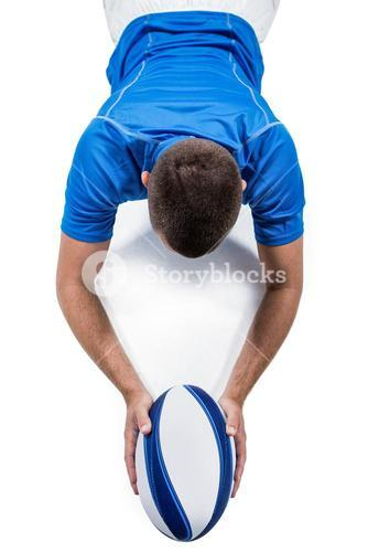 Rugby player lying in front with ball