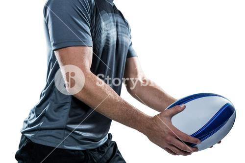 Midsection of rugby player in black jersey holding ball