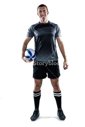 Full length portrait of smiling rugby player in black jersey holding ball
