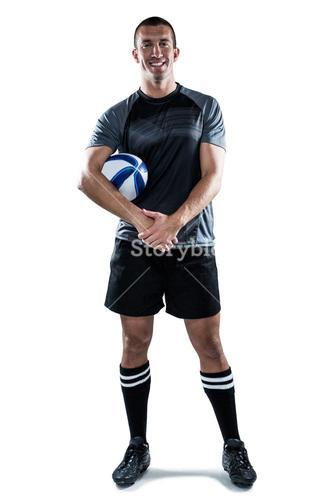 Smiling rugby player in black jersey holding ball with hands clasped