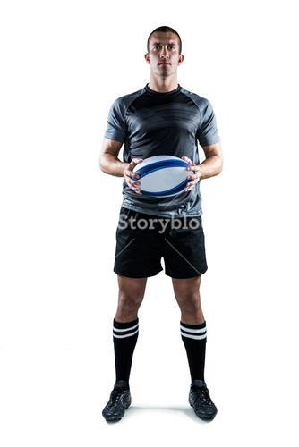 Serious rugby player in black jersey holding ball