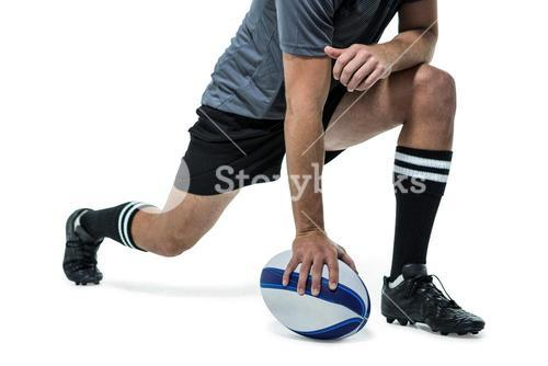 Rugby player in black jersey stretching with ball