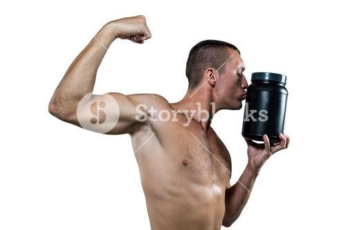Athlete flexing muscles while kissing nutritional supplement container