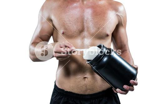 Midsection of shirtless man scooping up protein powder