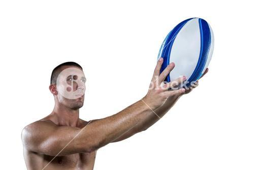 Shirtless rugby player holding ball
