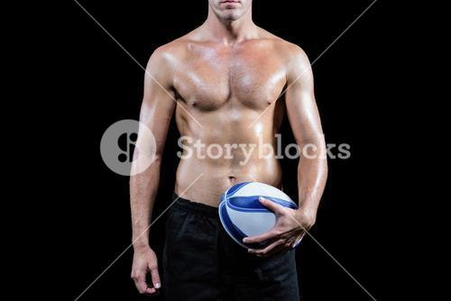 Midsection of shirtless sports player holding ball