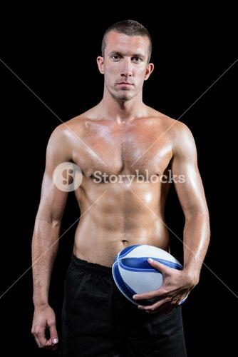 Confident shirtless sports player holding ball