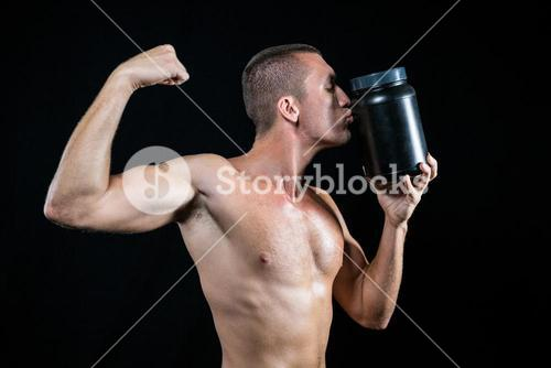 Athlete flexing muscles while kissing container