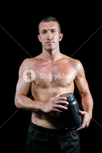 Portrait of handsome shirtless man holding nutritional supplement