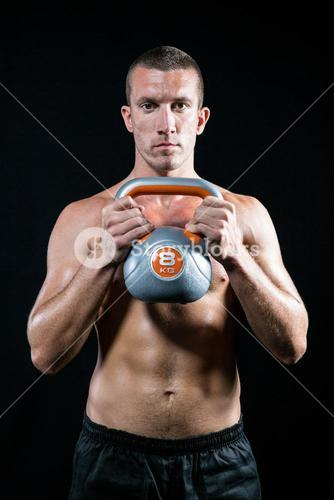 Confident shirtless athlete working out with kettlebell