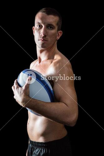 Portrait of handsome shirtless sports player holding ball