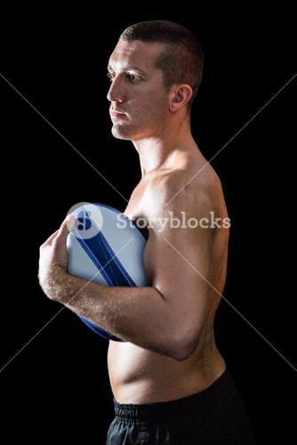 Handsome shirtless sports player holding ball