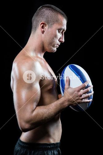 Thoughtful handsome shirtless sports player holding ball