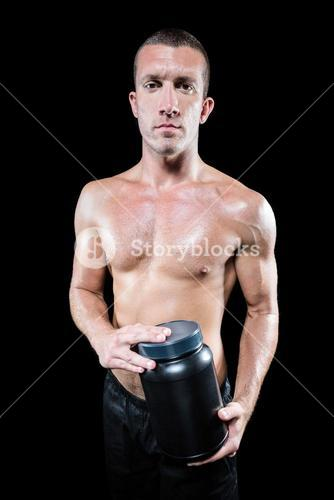 Portrait of confident shirtless man holding nutritional supplement