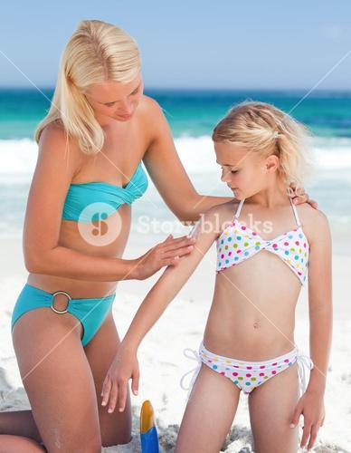 Mother applying sun cream on her daughter