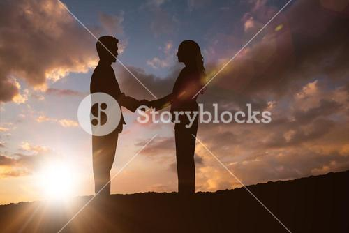 Composite image of silhouette of business people shaking hands