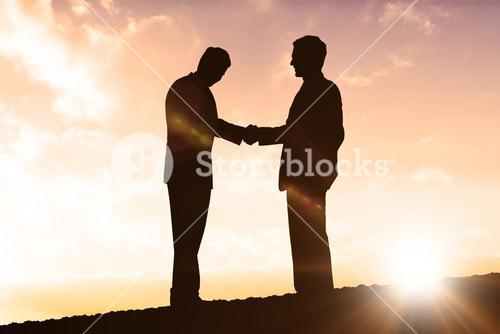 Composite image of silhouettes shaking hands