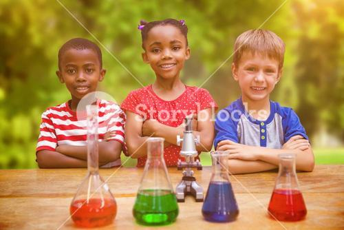 Composite image of cute pupils standing with arms crossed behind beaker