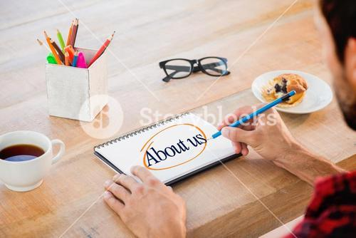 About us against creative businessman writing notes on notebook