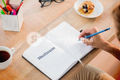 Maximum against man writing notes on diary