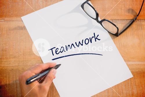 Teamwork against left hand writing on white page on working desk