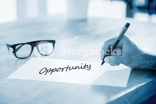 Opportunity  against side view of hand writing on white page on working desk