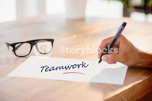 Teamwork against side view of hand writing on white page on working desk
