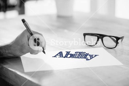 Ability  against side view of hand writing on white page on working desk