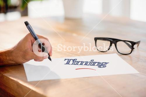 Timing against side view of hand writing on white page on working desk