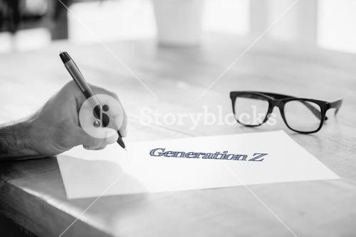 Generation z against side view of hand writing on white page on working desk
