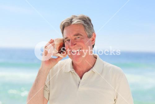 Senior man listening his shell