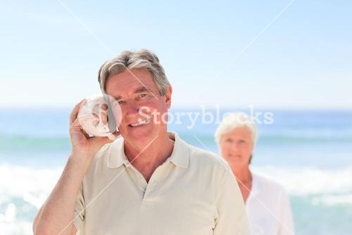 Man listening his shell with his wife behind him