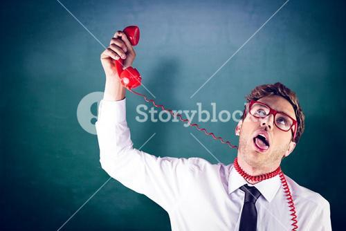 Composite image of geeky businessman strangling himself with telephone