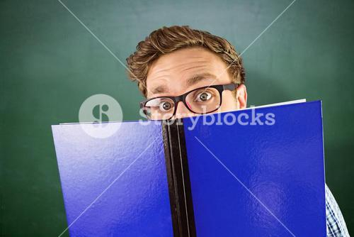 Composite image of geeky student reading a book