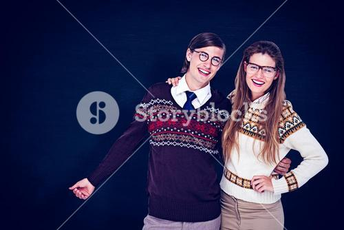 Composite image of happy geeky hipster couple embracing