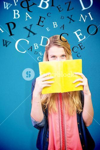 Composite image of student covering face with book in library