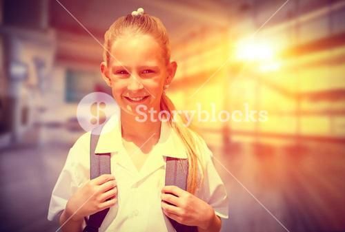 Composite image of cute pupil smiling at camera by the school bus