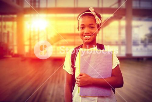 Composite image of little girl holding folders in school corridor