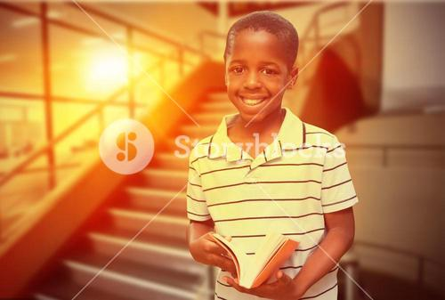 Composite image of happy pupil with book