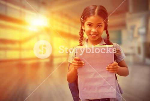 Composite image of cute pupil smiling at camera holding notepad