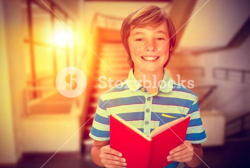 Composite image of cute pupil smiling at camera in library
